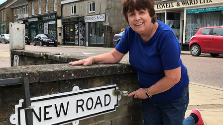Cllr Julie Smith next to the New Road sign in Chatteris she has worked on in a bid to revive some of