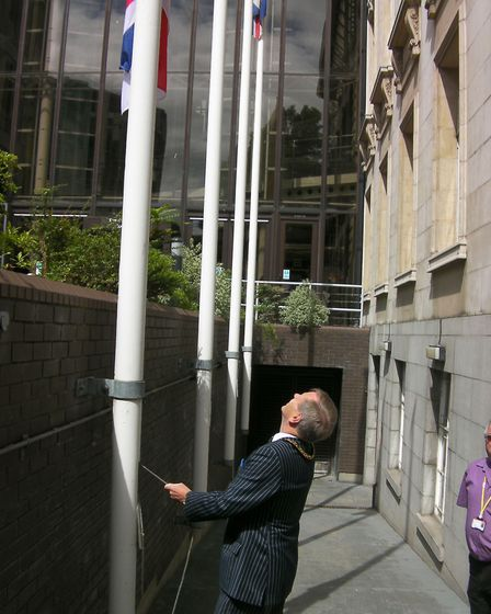 Cllr Rodney Bass in 2011, raising the Armed Forces Day flag