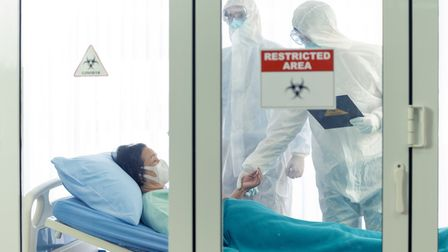 patient in bed, two medics in PPE