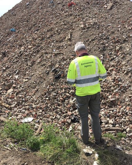 An enforcement officer inspecting a large pile of construction and demolition waste at the site in C
