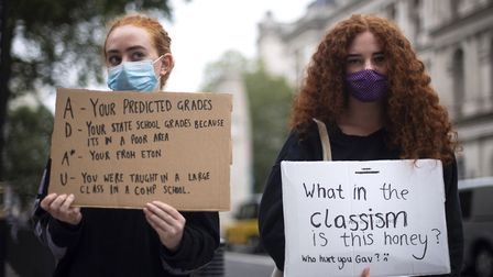 Students wearing face masks take part in a protest in Westminster in London over the government's ha