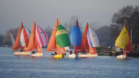 The Squib fleet, with spinnakers hanging limply, at the start of the first run at Oulton Broad.