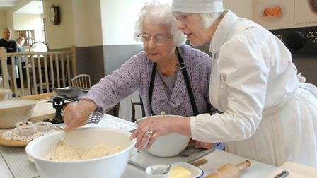 Former Blickling Hall cook Flo Wadlow gives volunteer re-enactor Bunty Gotts guidance on how things