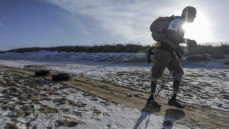 Double amputee Sgt Duncan Slater trains on the snow covered beach pulling some tyres. Picture Matthe