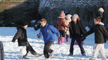 Children play in the snow at Sheringham Primary School, which has not closed because of bad weather