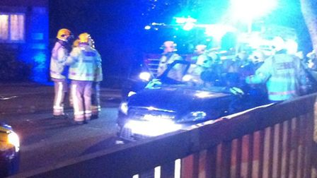 Firefighters cut away the roof of a taxi after a crash in Rouen Road.