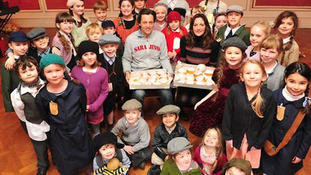 Youngsters from Somerleyton Primary school receive penny buns from Hugh and Lara Crossley at Somerle