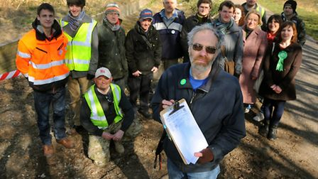 County Councillor Richard Bearman holds the petition at the former Norwich City Station site with su
