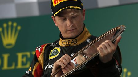 Kimi Raikkonen looks down on his spoils after taking a superb win in the first grand prix of the 201