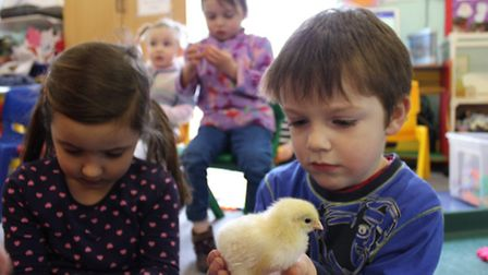 Four-year-olds Phoebe Kett and Oliver Wood with an Easter chick hatched at Ladybird Nursery, Shering