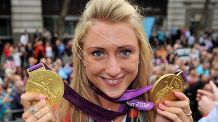 Cyclist Laura Trott shows her gold medals as she takes part in a parade through London, celebrating