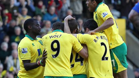 Ryan Bennett is mobbed by his Norwich City team-mates after his opener agains Reading. Picture by Pa