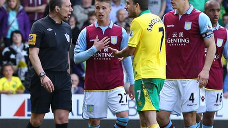 Aston Villa's Joe Bennett, centre, protests his innocence to referee Kevin Friend after he has a pen