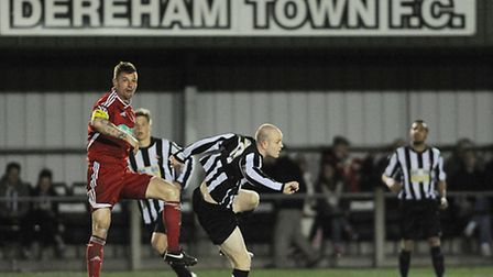 Wisbech Town, in red, will not be playing higher-level football alongside Dereham Town next season.