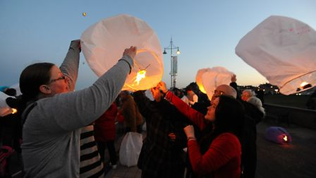 People on the promenade in Lowestoft releasing lanterns into the evening sky in memory of Fiona Ande