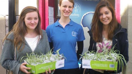 Exmouth Raptors Aine Casey and Eliza Palmer make a presentation to Holly Keating of Headway Devon.