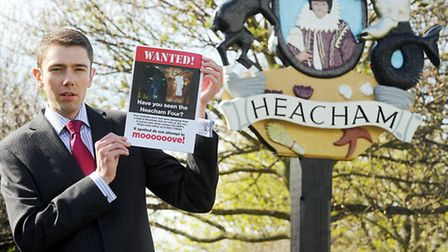 EDP Reporter Andrew Papworth with the wanted poster for the escaped herd by the village sign in Heac