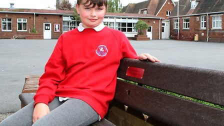 Exeter Road pupil Lily Robbins sitting on 'Caroline's Bench' dedicated in memory of Lily's mother. P