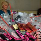 Trading Standards team leader, Alice Barnes, with a pile of bags full of counterfeit designer make-u