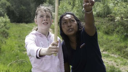 Tia Sweetings, assistant warden, teaches Eva Squires how to measure the height of trees using trigon