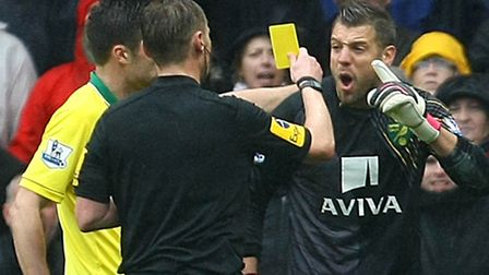 Referee Mike Jones rubs salt into the wounds by giving Mark Bunn a yellow card after awarding a pena