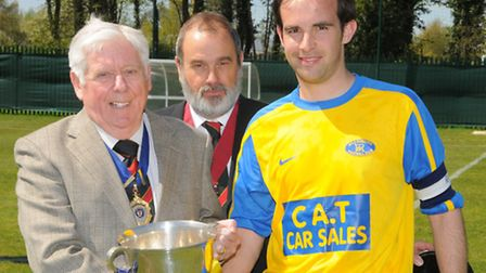 Acle Rangers captain Peter Nobbs receives the trophy from league president Ray Kiddell, watched by c