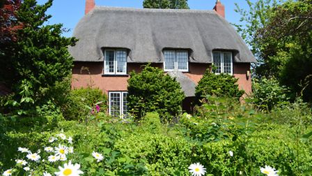 A charming grade II listed detached thatched cottage occupying wonderful private gardens of around 1