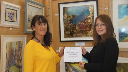 Anna Fitzgerald being awarded her prize for her work titled 'Heading Home' by a representative from