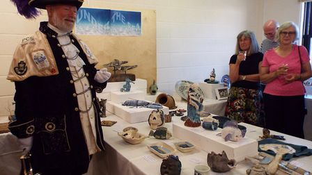 Roger Bourgein, Exmouth's town crier, officially opens the Exmouth Ceramic Group exhibition at the E