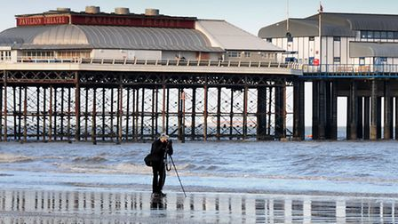 A photographer takes advantage of the blue, cloudless sky over Cromer Pier and beach today.PHOTO: AN