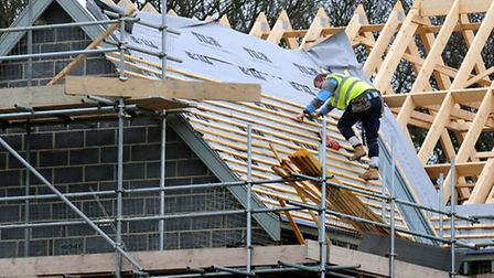 File photo dated 28/2/12 of a general view of roof workers building new houses in Derbyshire, as the