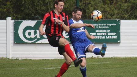 Exmouth Town's Steve Avery comes under challenge from Cullompton Rangers player Lewis White during t