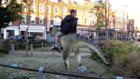A youth photographed riding one of Exmouth's model dinosaurs.