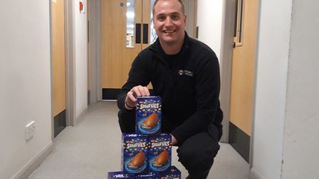 Exmouth probation firefigher Nelly takes charge of a donation of Easter eggs from Exmouth ABC Day Nu