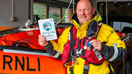 Deputy 2nd coxswain Roger Jackson with a copy oif Surviving the Storm and his RNLI Bronze Medal for