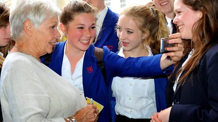 Dame Judi Dench surrounded by schoolchildren at Norwich cathedral during her visit to the city. Pho