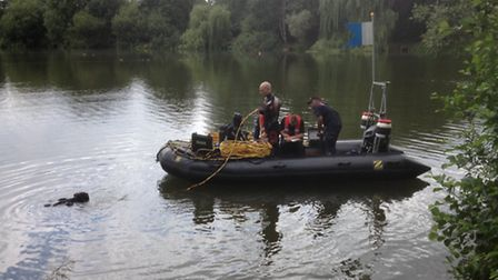 Divers search a section of the UEA Broad where the body of a woman was discovered last week. Picture