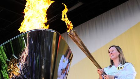 Charlotte Peck lights the Olympic Cauldron with her torch at the Chapelfield Gardens stage show. Pic