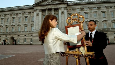 The Queen's Press Secretary Ailsa Anderson with Badar Azim a footman place on an easel in the Forecourt of Buckingham...