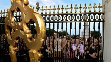 The large waiting crowds cheers as they read the news on an easel in the Forecourt of Buckingham Pal