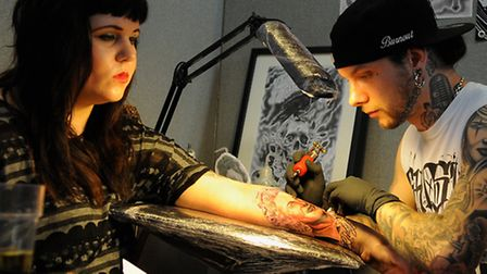 Justin Burnoud of the Ghost House Collective, tattoos Emma Courridge at the Body Art Festival at St