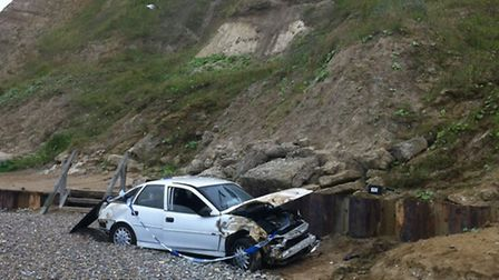 The car pictured at the bottom of the cliff on Sunday morning