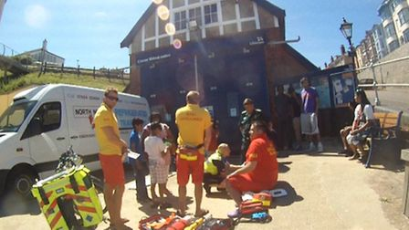 Rescuers help a woman who fell and hurt her head on Cromer promenade. Picture: RNLI