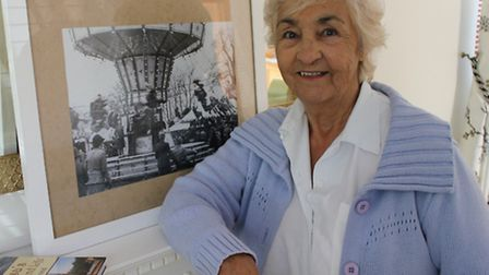 """Louisa Prestney pictured at her Sheringham home in front of a photograph of the """"Chair-o-Planes"""" fai"""