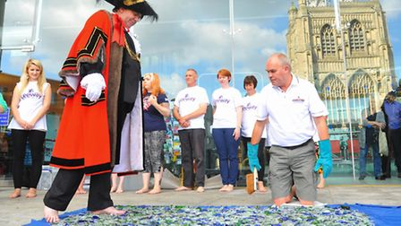 Lord Mayor of Norwich Keith Driver walking on broken glass in aid of domestic violence charity Leewa