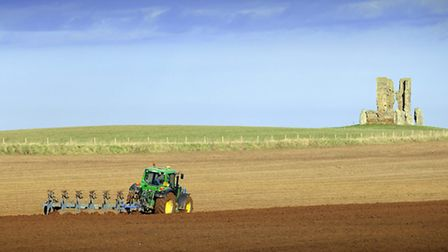 A tractor ploughing a field near Bawsey Ruin.