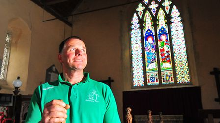 Church warden Alan Beck with the east window at St Peter's Church, Brumstead, near Stalham, which ha
