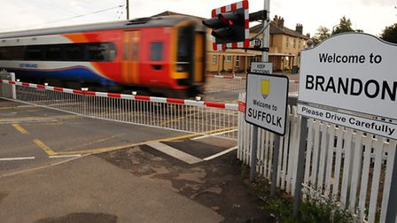 A train flashes past the new barriers at the level crossing on Bridge Street in Brandon. Photograph