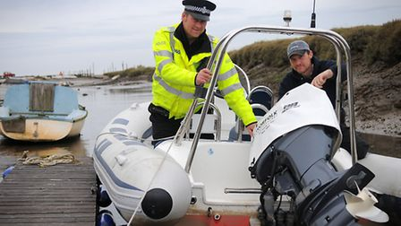 Outboard motor thefts at Morston Quay. PC Jason Pegden with boatyard owner Neil Thompson with a police outboard cover.