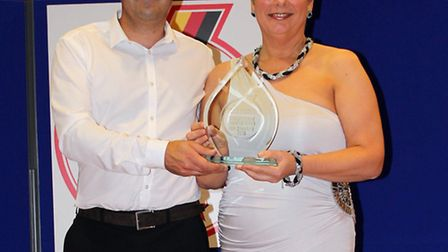 Neil Crayford, owner of Norfolk Performance Car Sales, collects his award from Sally Appleby, production manager of Audi...